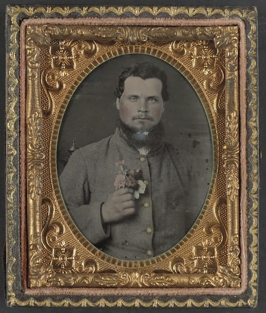 [Unidentified soldier in Confederate uniform with bouquet of flowers]