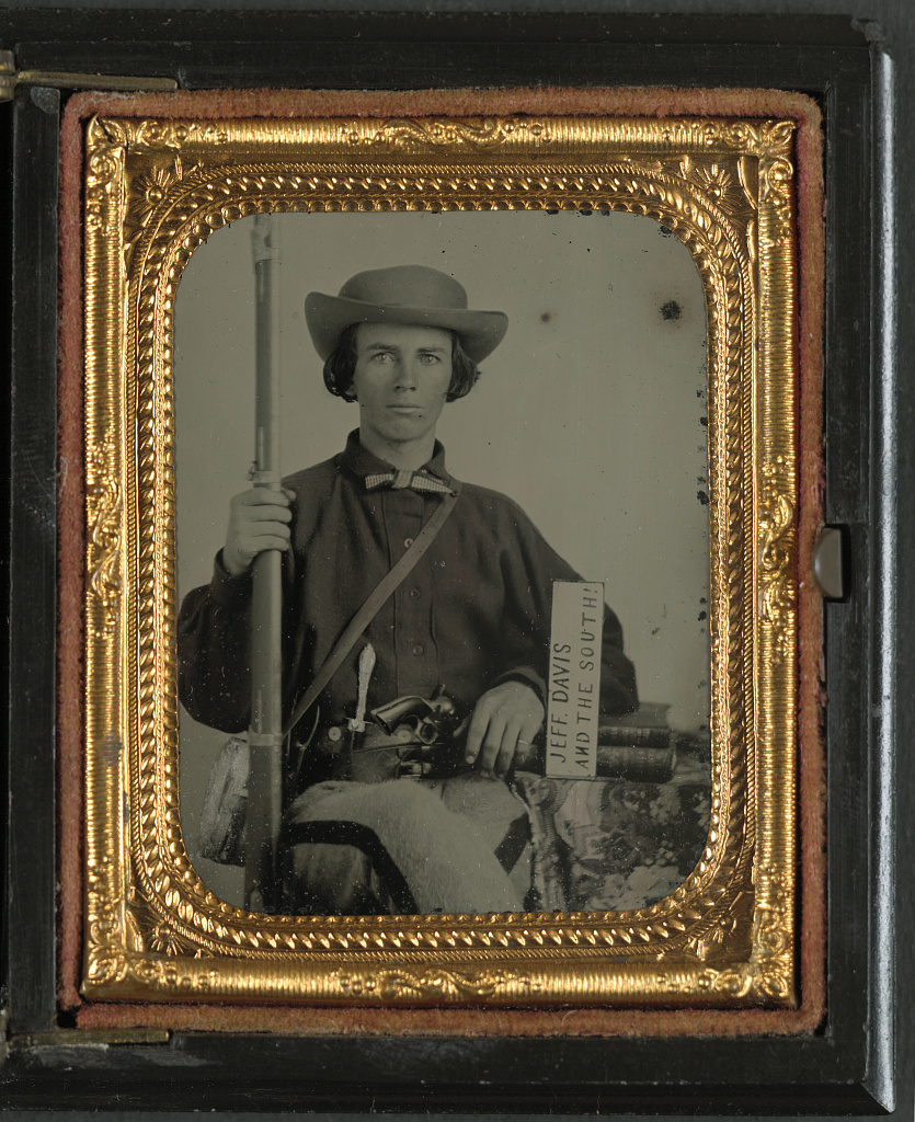[Unidentified soldier in Confederate uniform with rifle musket, revolver, side knife, canteen, and sign reading Jeff Davis and the South!]