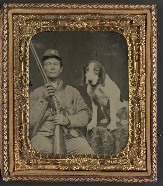 [Unidentified soldier in Confederate uniform with shotgun sitting next to dog]