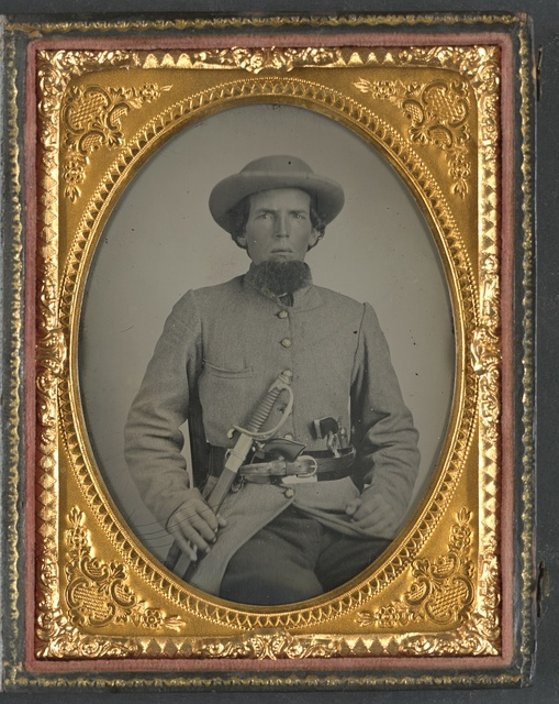 [Unidentified soldier in Confederate uniform with sword and two guns]