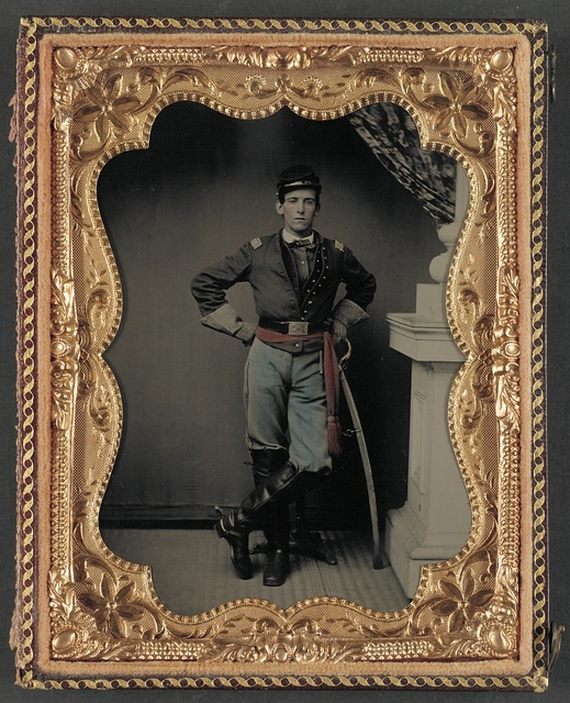 [Unidentified soldier in first lieutenant's uniform, red sash, leather gauntlets, and spurs with cavalry sword]
