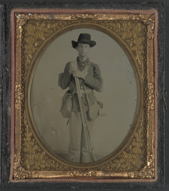 [Unidentified soldier in uniform with musket, canteen, cup, and haversack; either Confederate or Union]