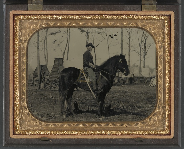 [Unidentified soldier in Union cavalry uniform, on horse, with cavalry saber, in front of encampment with winter chimneys]