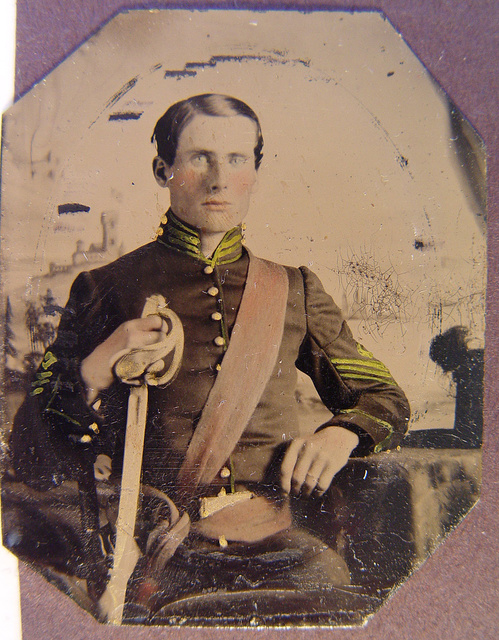 [Unidentified soldier in Union first sergeant's uniform with cavalry saber in front of painted backdrop showing landscape]