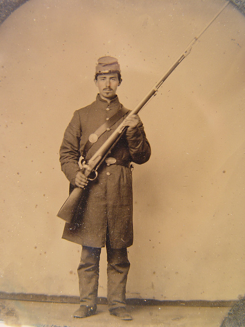 [Unidentified soldier in Union frock coat and forage cap with bayoneted musket]