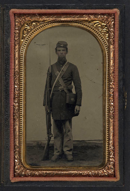 [Unidentified soldier in Union frock coat and forage cap with cap box, cartridge pouch, and bayoneted musket]