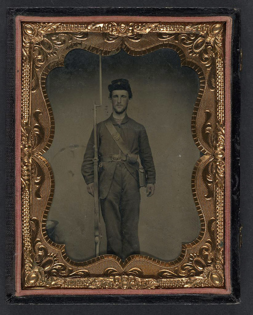[Unidentified soldier in Union frock coat and forage cap with cartridge pouch, ammunition pack, and bayoneted musket]