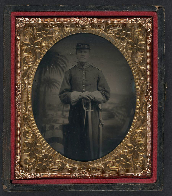 [Unidentified soldier in Union frock coat, forage cap, shoulder scales, and gauntlets with sword and scabbard in front of painted backdrop showing landscape with palm trees]