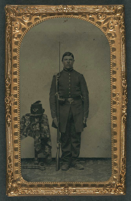 [Unidentified soldier in Union frock coat with bayoneted musket next to infantry Hardee hat with plume on table]