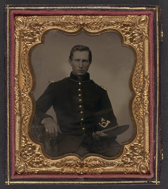[Unidentified soldier in Union infantry uniform with shoulder scales holding Hardee hat with Company A insignia]