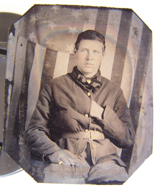[Unidentified soldier in Union sack coat in front of American flag backdrop]