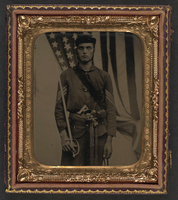 [Unidentified soldier in Union sergeant uniform and sash with Model 1840 non-commissioned officer's sword, revolver, cap box, and knife in front of American flag]