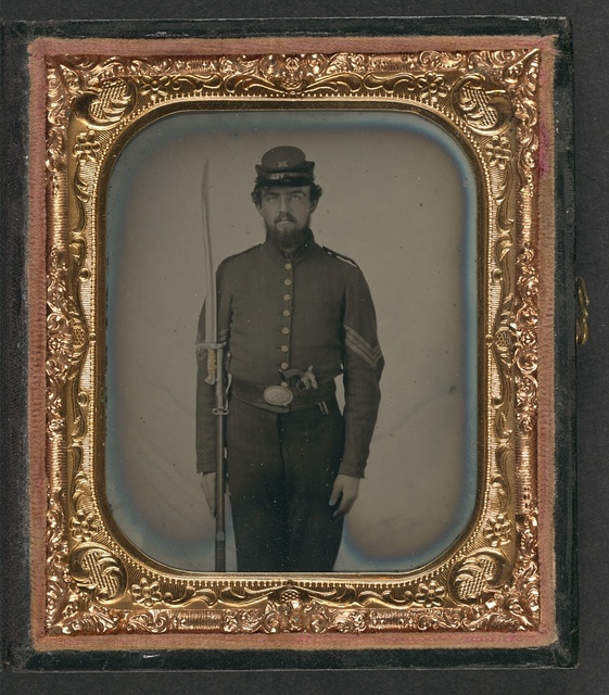 """[Unidentified soldier in Union sergeant's uniform and Company H forage cap with revolver, musket, and attached U.S. Model 1862 """"Zouave"""" sword bayonet]"""