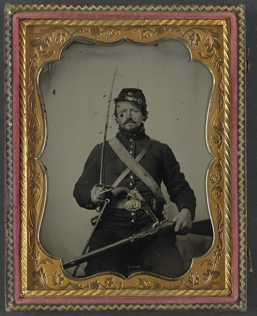 [Unidentified soldier in Union uniform and Company B hat, with Hall breech loading carbine rifle, Colt revolver, and cavalry sword]