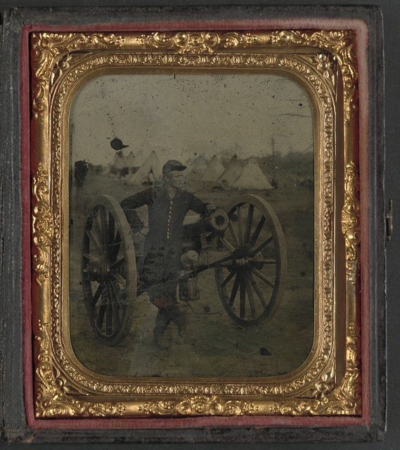 [Unidentified soldier in Union uniform standing with Napoleon cannon in front of encampment]