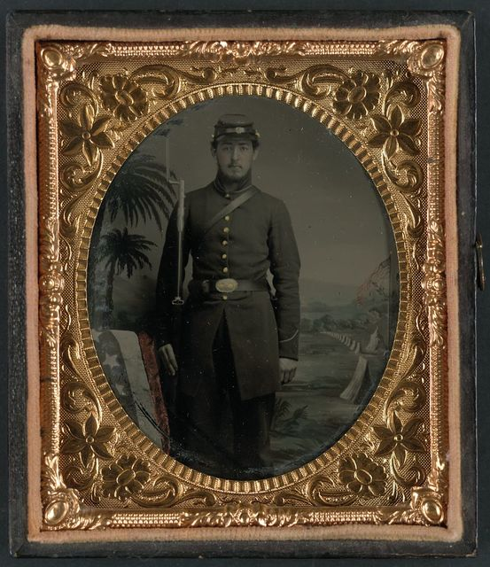 [Unidentified soldier in Union uniform with bayoneted musket in front of painted backdrop showing encampment with palmetto trees and American flag]