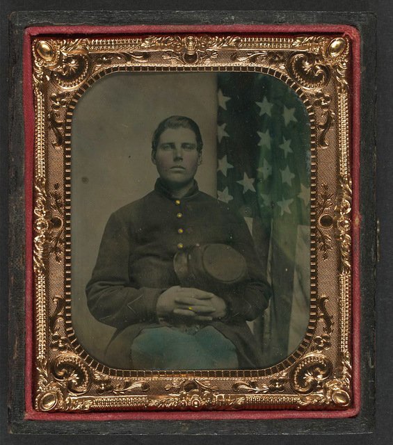 [Unidentified soldier in Union uniform with forage cap in front of American flag]