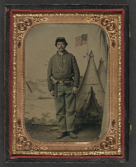 [Unidentified soldier in Union uniform with revolver in holster in front of U.S. Picture Tent painted backdrop]