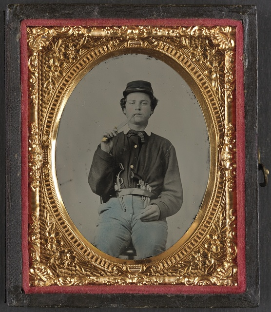[Unidentified soldier in Union uniform with two revolvers and picking his teeth with a Bowie knife]