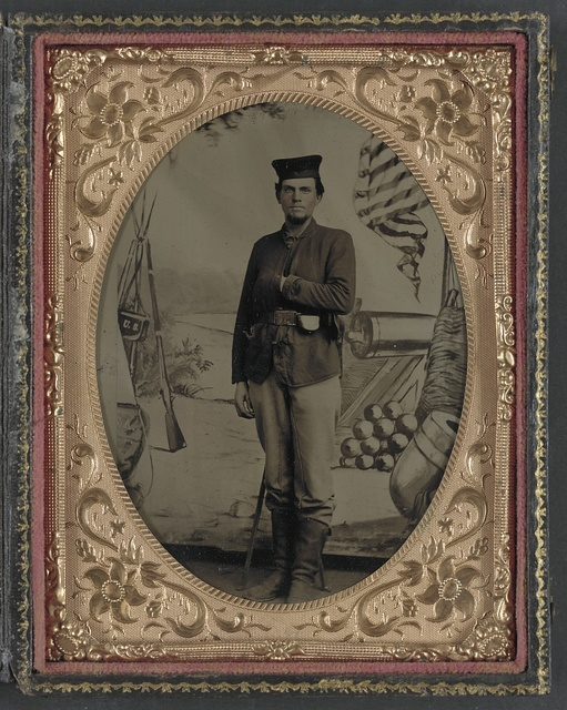 "[Unidentified soldier of ""First Scotch Regiment,"" 12th Illinois Infantry Regiment, in sack coat and Tam o'Shanter cap in front of painted backdrop showing weapons and American flag at Benton Barracks, Saint Louis, Missouri]"