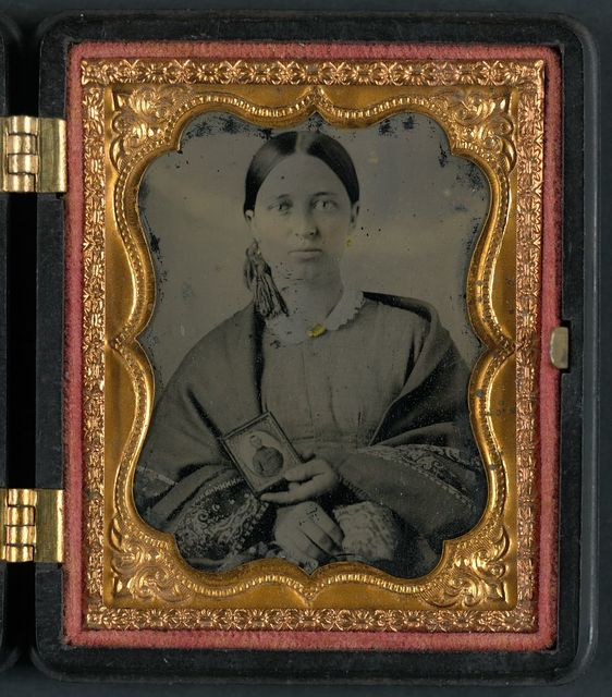 [Unidentified woman holding a cased photograph of an unidentified soldier in Confederate uniform]