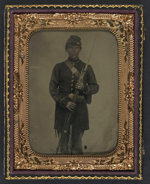 [Unidentified young soldier in Union frock coat and forage cap with bayonet scabbard, cartridge pouch, ammunition box, and bayoneted musket]