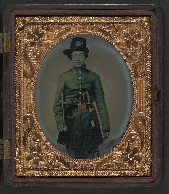 [Unidentified young soldier in Union frock coat and infantry Hardee hat with sword, revolver, and fife]