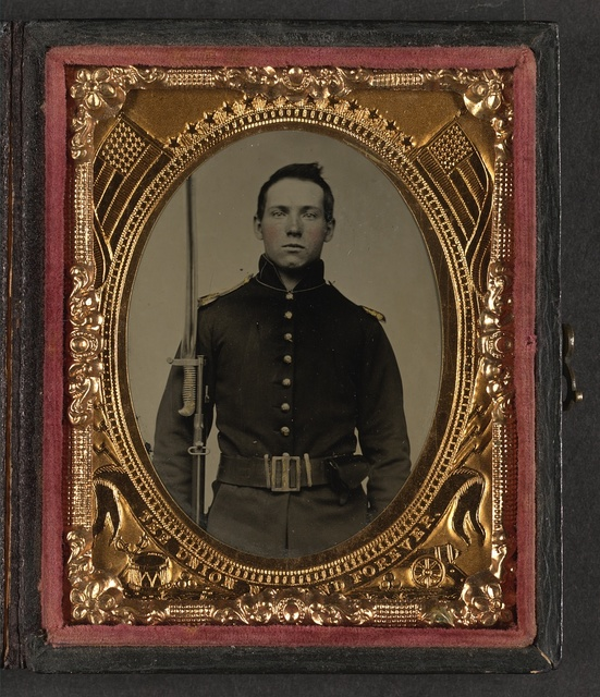 [Unidentified young soldier in Union rifleman's uniform and shoulder scales with musket and attached U.S. Model 1862 sword bayonet]