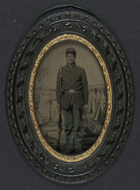 [Unidentified young soldier in Union sack coat and forage cap with bayonet scabbard and bayoneted musket in front of painted backdrop showing military camp]