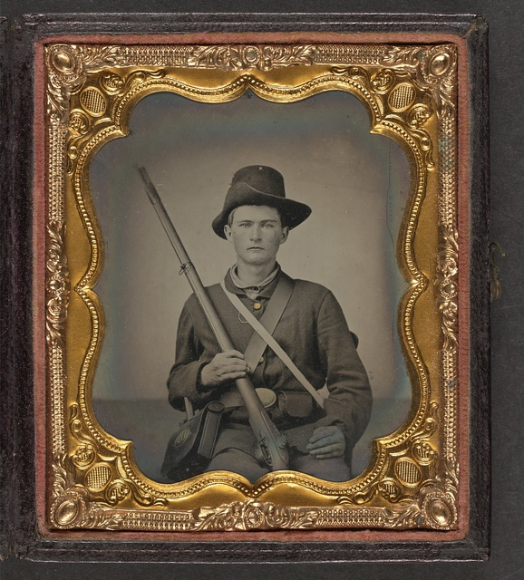 [Unidentified young soldier in Union uniform and Hardee hat sitting with musket, cartridge box, and cap box]
