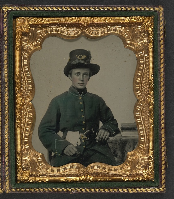 [Unidentified young soldier in Union uniform and plumed Hardee hat with plain gauntlets and revolver sitting next to table with books]