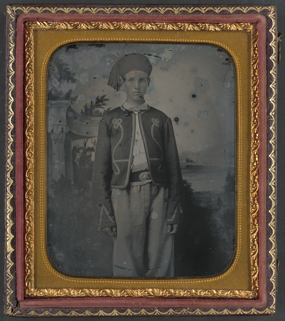 [Unidentified young soldier in Union Zouave uniform in front of painted backdrop showing a pavillion at the edge of a lake]