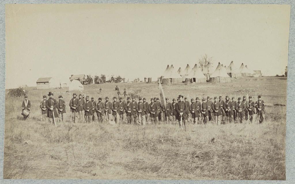 [Union soldiers lined up in the field with tents in the background]