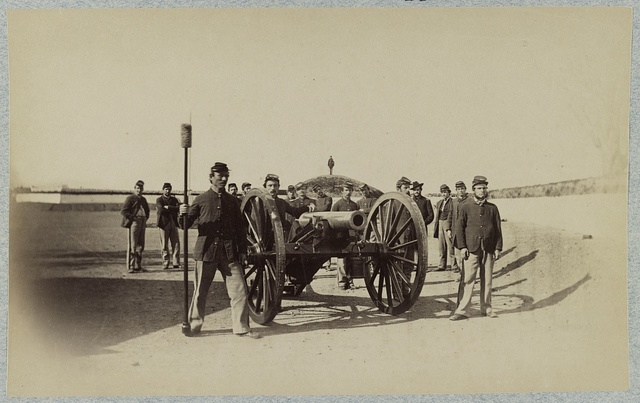 [Union soldiers stand around a mounted cannon at a fort]