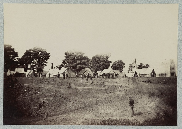 [Union soldiers stand in front of their camp]
