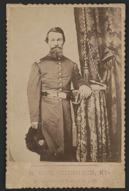 [Captain John Wilson of Co. C, 8th Kentucky Infantry Regiment (Union), in uniform with sword; revolver and book rest on table]
