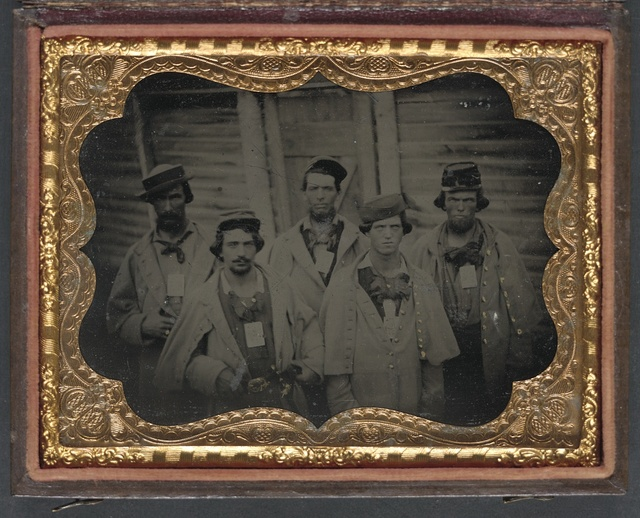 [Five unidentified prisoners of war in Confederate uniforms in front of their barracks at Camp Douglas Prison, Chicago, Illinois]