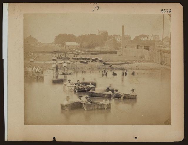 [Military construction in northern Virginia: men sitting in blanket boats on the Potomac River]