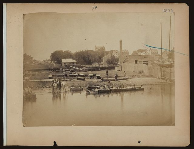 [Military construction in northern Virginia: men sitting in blanket boats strapped together on the Potomac River]