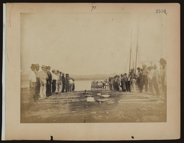 [Military construction in northern Virginia: men standing on Potomac River bank with blanket boat frames not yet assembled]