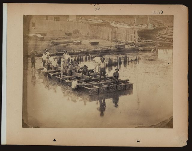 [Military construction in northern Virginia: raft of blanket boats ferrying men and timber across the Potomac River]