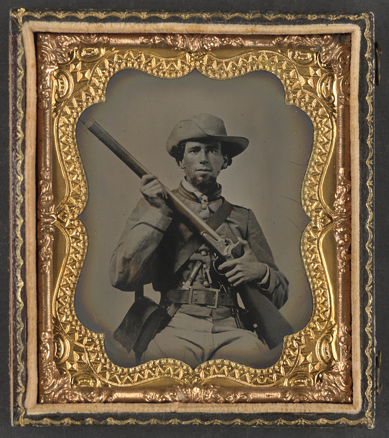 [Private John P. Alldredge of Co. A, 48th Alabama Infantry Regiment in uniform and wishbone belt buckle with Model 1842 rifle musket, revolver, and side knife]