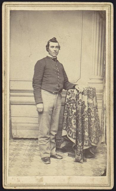 """[Theodore H. Marsh, Co. """"L"""" 27 New Jersey, full-length studio portrait, standing with left arm resting on studio prop, facing slightly right, wearing military uniform]"""