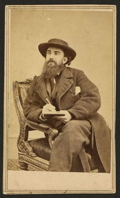 [Alfred Waud, full-length portrait, seated, holding a pencil and pad, facing left]