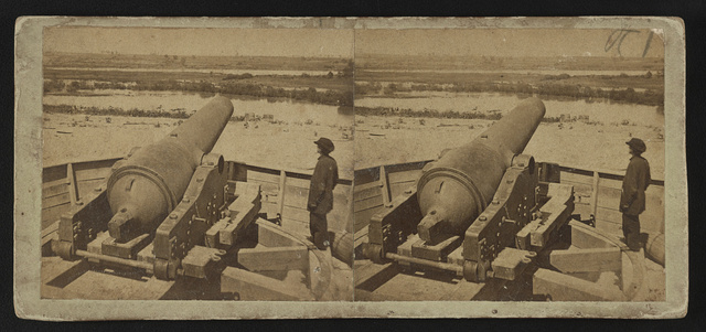 [Inside the battery, a man stands next to a cannon aimed at the river]