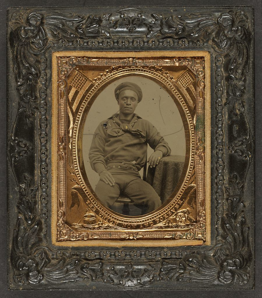 [Unidentified African American sailor in Union uniform sitting with arm resting on table]