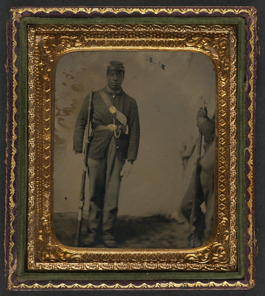 [Unidentified African American soldier in Union uniform and gloves with musket; another soldier waits at the side]