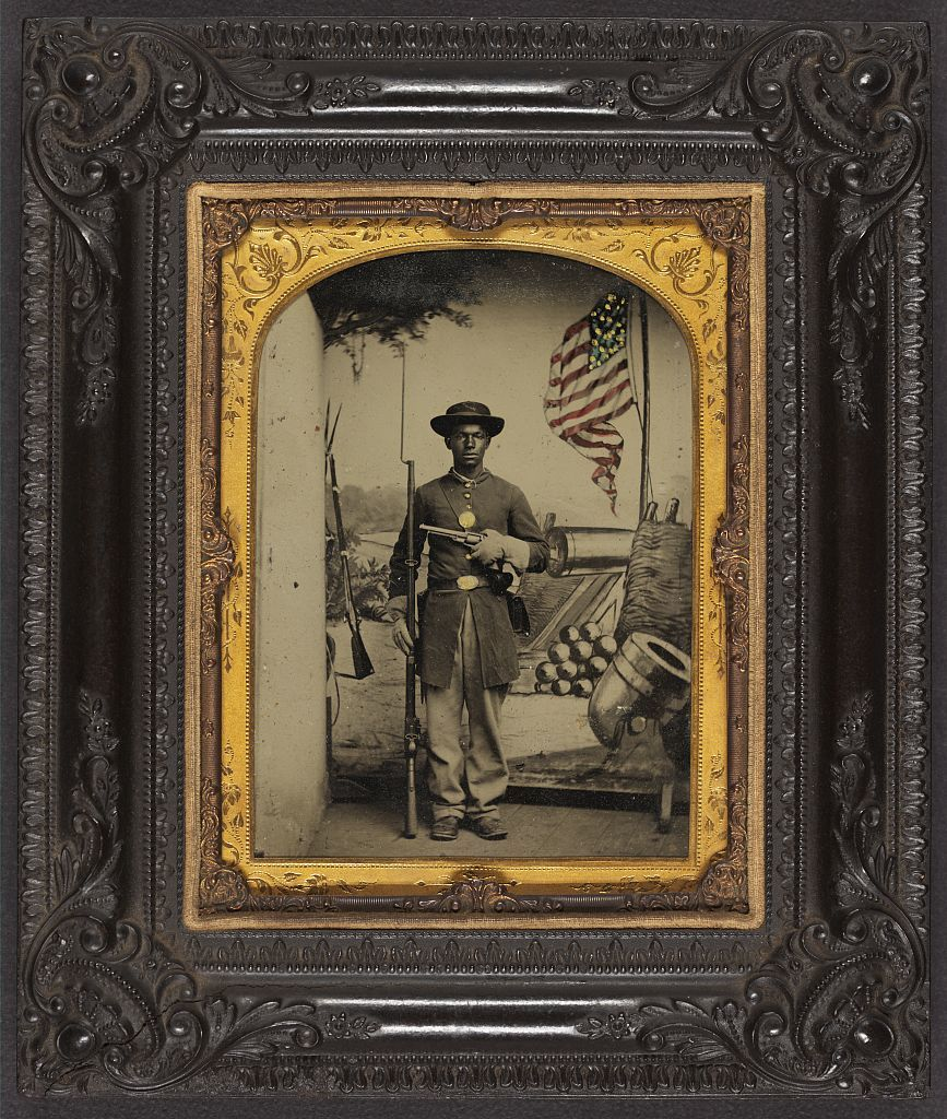 [Unidentified African American soldier in Union uniform with a rifle and revolver in front of painted backdrop showing weapons and American flag at Benton Barracks, Saint Louis, Missouri]