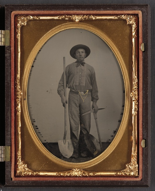 [Unidentified man with gold mining equipment and wearing a U.S. beltplate]