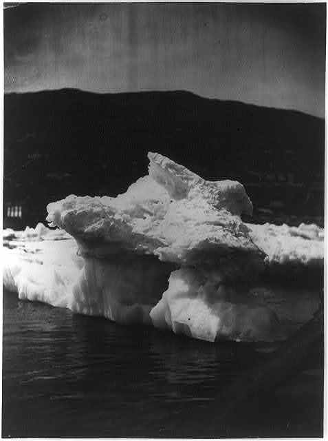 [Another view of iceberg or ice formation with hole at center, off the coast of Labrador, with land visible in the background]